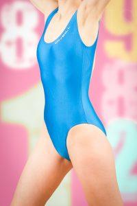 Model trägt hellblau glänzenden Badeanzug